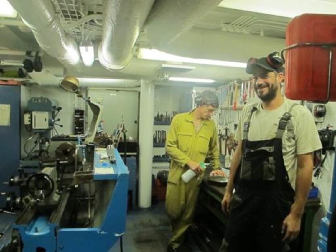 Greg, second mécanicien et Max, officier mécanicien, dans l'atelier mécanique adjacent à la salle machine.